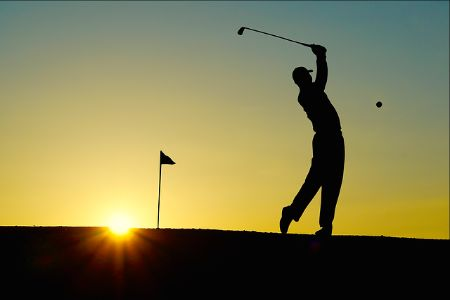 golfer playing at sunset